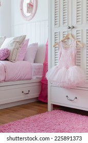 girl's pink dress hanging on wardrobe in bedroom at home