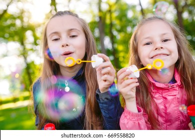 Girls play with soap bubbles.
