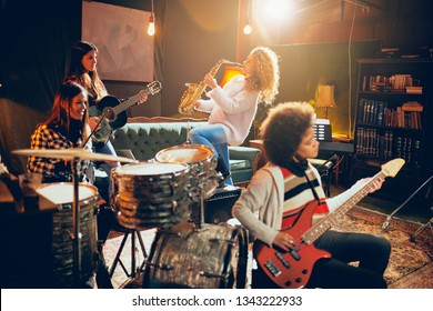 Girls playing jazz music. In foreground one woman playing bass guitar and in background other two playing saxophone and drums. Home studio interior.
