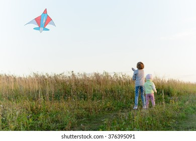 Girls playing with a kite in the spring