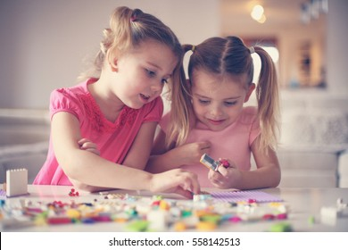 Girls playing with Lego blocks at home.