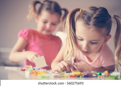 Girls playing with Lego blocks at home. Focus on one girl.