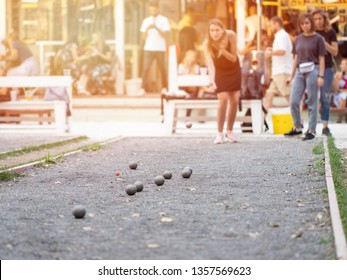 Girls playing petanque against retro style cafe on a sunset