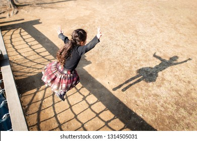 Girls playing with their own shadow