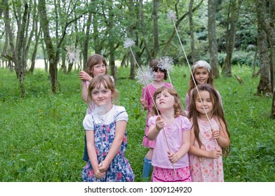 Girls playing with wands in a wood