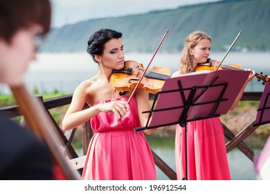 Girls plays violin outdoors near the river