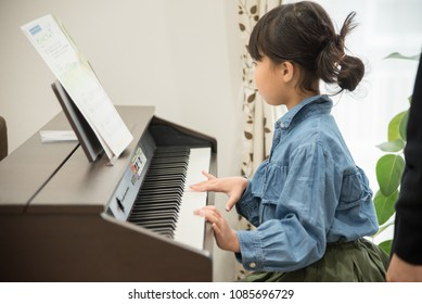 Girls practicing piano in the living room