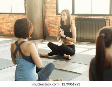 Girls practicing yoga with instructor, sitting in Sukhasana exercise with namaste gesture, Easy Seat pose, women's practice concept