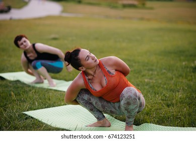 Girls practicing yoga in the park during sunset. Healthy lifestyle.
