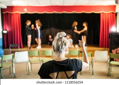 girls praising a theater class before the look of her blonde teacher on her back