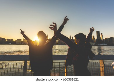 Girls with raised hands at sunset in New York. Successful and happy young women enjoying the sun setting behind skyscrapers in Manhattan. Travel and lifestyle concepts