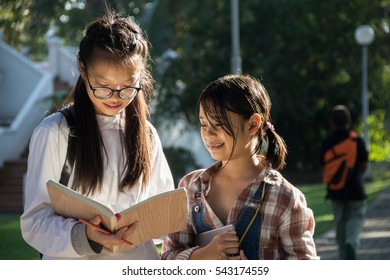 Girls reading book and smile with blurred background