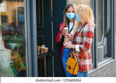 Mädchen, die Kaffee aus dem Coffeeshop im Freien während der Quarantäne erhalten. Zwei Frauen im Gesicht maskieren die Fußgängerstadt. Freunde reisen zusammen in der Stadt. Sommerurlaub während der Koronavirus-Pandemie.