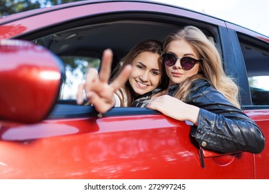 Girls in the red car. Little holiday trip of friends