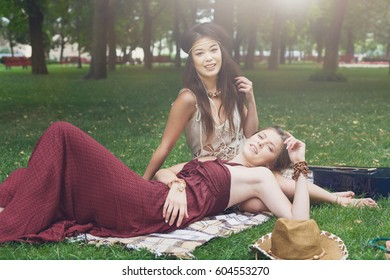 Girls relax in summer park, young hippie friends leisure