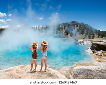 Girls  relaxing and enjoying beautiful view of gazer on vacation hiking trip. Friends on hiking trip. Excelsior Geyser from the Midway Basin in Yellowstone National Park. Wyoming, USA