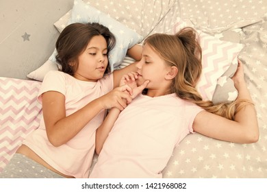 Girls relaxing on bed. Slumber party concept. Girls just want to have fun. Invite friend for sleepover. Best friends forever. Consider theme slumber party. Slumber party timeless childhood tradition.