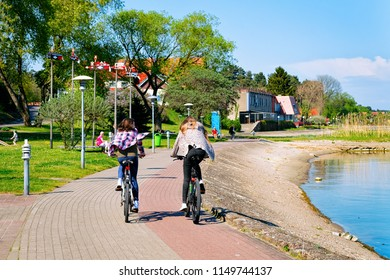 Girls riding a bicycle. Nida resort town near Klaipeda in Neringa, in the Curonian Spit and the Baltic Sea in Lithuania.