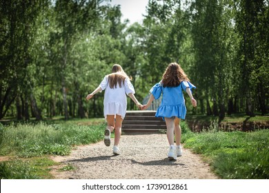 girls run hands long hair sneakers dresses sundresses blue white green nature park walk trees stairs road together go into the distance