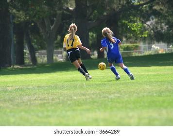 Girls running after a ball playing soccer