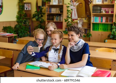 Girls at school desks. Girlfriends are sitting at school with books, notebooks and telephones. Children study in the school room