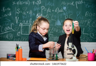 Girls school uniform busy with proving their hypothesis. School project investigation. School experiment. Science concept. Gymnasium students with in depth study of natural sciences. Private school.