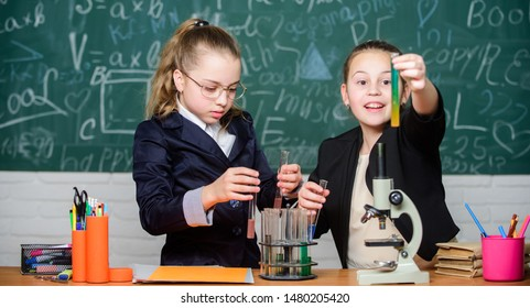 Girls school uniform busy with proving their hypothesis. Private school. School project investigation. School experiment. Science concept. Gymnasium students with in depth study of natural sciences.