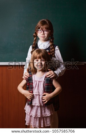 e47f9bd0ea79 girls in school uniform, sisters, an older example for a younger sister. In  the classroom on the background of a school board - Image
