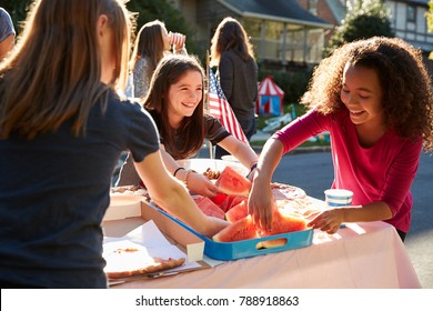Girls serving themselves watermelon at a block party