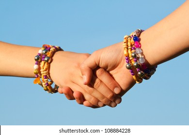 Girls shaking hands, children, close-up on blue background, sky