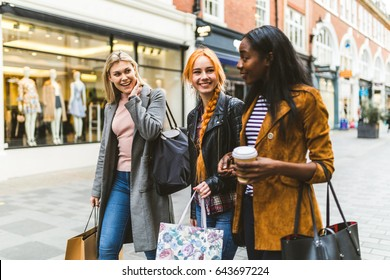 Girls shopping and walking in London. Three girls, multiracial group, having fun in the city while shopping. Best friends sharing happiness, lifestyle and friendship concepts