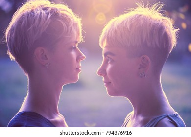 girls with short hair, face to face, park.