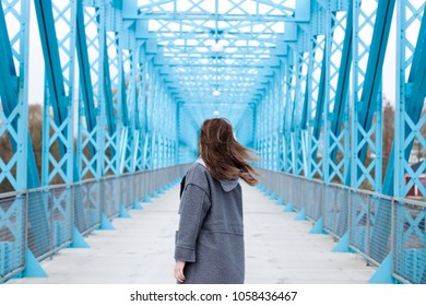Girl's silhouette on an unusual blue bridge made of metal. Interesting concept