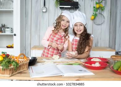 Girls, sisters, girlfriends, children prepare food in the kitchen.
