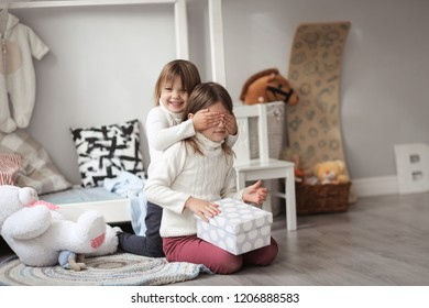 girls sisters in sweaters play in a real room in a bright interior, the concept of a happy childhood and holiday gifts.