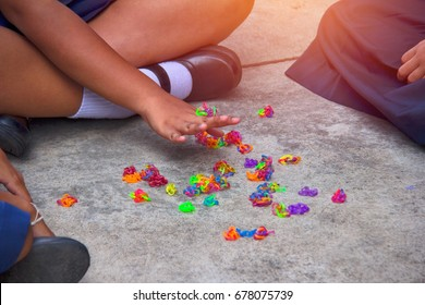 Girls sitting around the jackstones, Thai folk games : Thai folk games : Using plastic toys, many colors are fun devices.