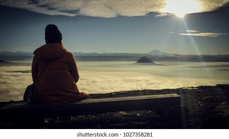 Girl's sitting on the bench above the cluds, sun and mountains.