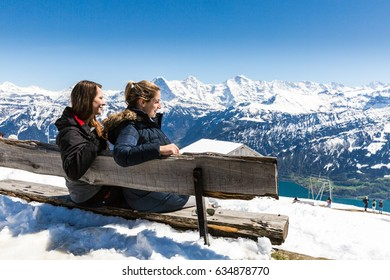 Girls sitting on a bench at the Niederhorn Beatenberg Mountain summit with the Bernese Alps in background