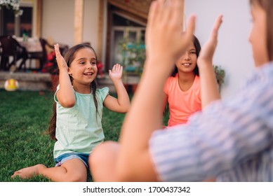 Girls sitting on the grass and playing hand-clapping games