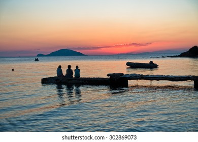 Girls sitting on a pier in front of small island at sunset, Sithonia, Greece
