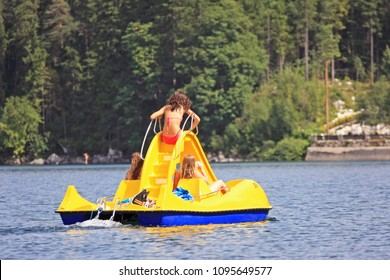Girls sitting on yellow boat with slide