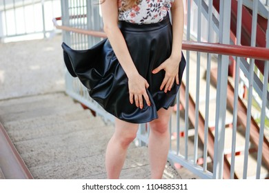 The girl's skirt rises in the wind. Black leather skirt