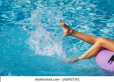 girls slim legs on the inflatable ring playing with water in the swimming pool. Summer Vacation. Enjoying suntan. Weekend on resort