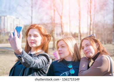 Girls smile and take a selfie together. Grimaces, wink and sign. Four girls, friends, smile and take a selfie together. The blonde girl raises her arms as a sign