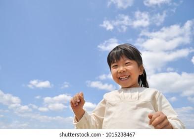 Girl's smiling in the blue sky