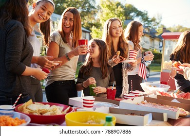 Girls stand talking at a block party food table, close up