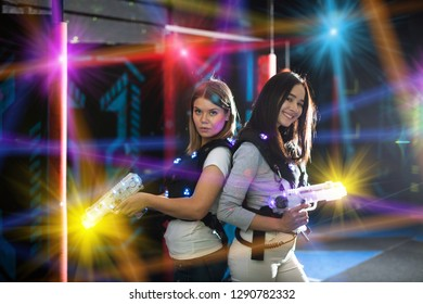 Girls standing back to back in colorful laser beams, holding guns during lasertag game in labyrinth