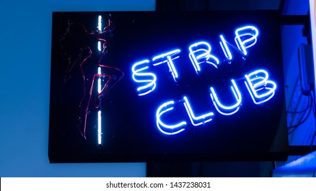 Girls strip club blue neon sign and woman silhouette