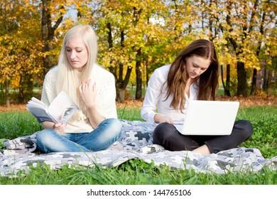 Girls study in autumn park