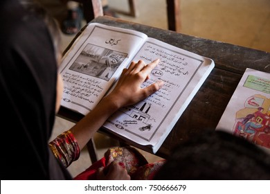 Girls Studying reading in a classroom. Thatta, Sindh, Pakistan - September 08 2015. Government Schools Condition.